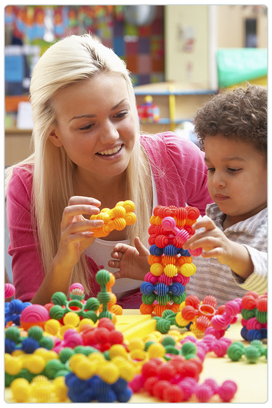 Young woman playing with boy in nursery school